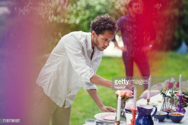 Young man lighting candles on table at garden party