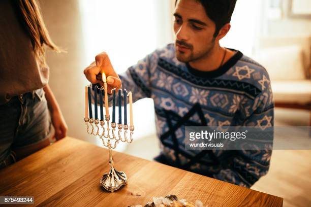 young man lighting candlesticks on menorah for jewish hannukah - hanukkah imagens e fotografias de stock