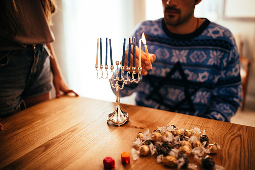 Young man lighting candlesticks on traditional jewish menorah for Hannukah 874103690
