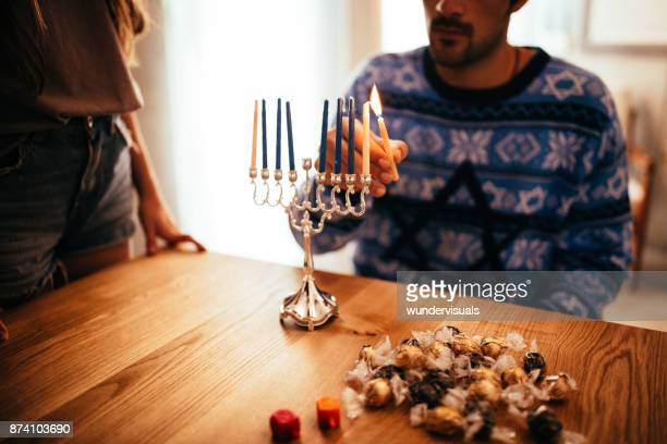 young man lighting candlesticks on traditional jewish menorah for hannukah - hanukkah imagens e fotografias de stock
