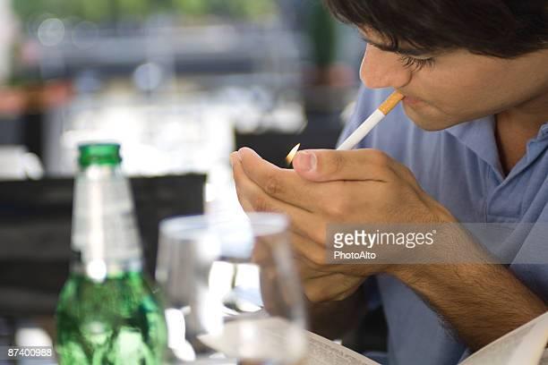 Young man lighting cigarette