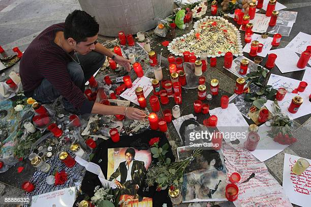 A young man lights candles at a makeshift memorial to late US popstar Michael Jackson at the same time as Jackson's funeral services in California on...
