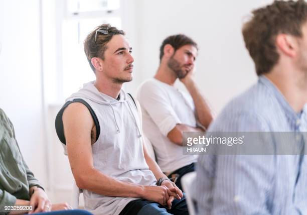 Young man listening in group therapy session