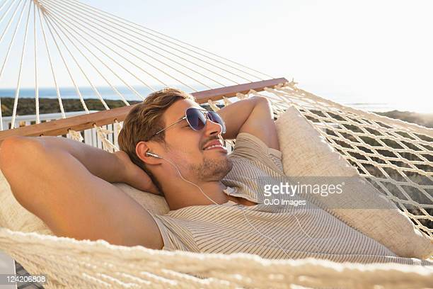 Young man listening music and relaxing in hammock