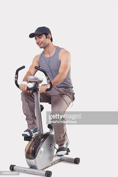 Young man listening music while exercising over white background