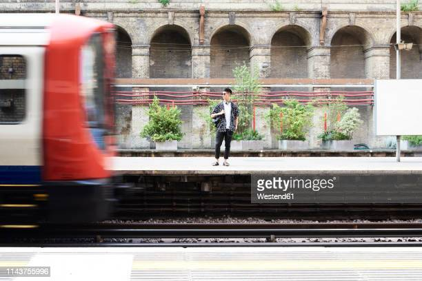 young man listening music with headphones, standing on station - london underground stock pictures, royalty-free photos & images