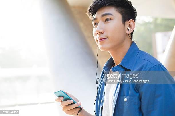 Young man listening to earphones