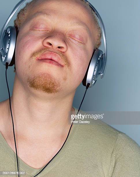 Young man listening to headphones, eyes closed, close-up