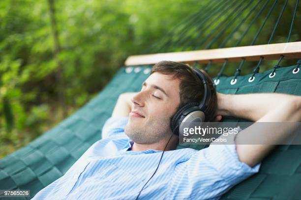 young man listening to headphones - wildnisgebiets name stock pictures, royalty-free photos & images
