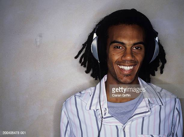 Young man listening to headphones, smiling, portrait