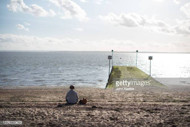 A young man listening to his earphones relaxes in the sunny weather on Chalkwell beach on October 22 2020 in Chalkwell SouthendonSea England Southend...