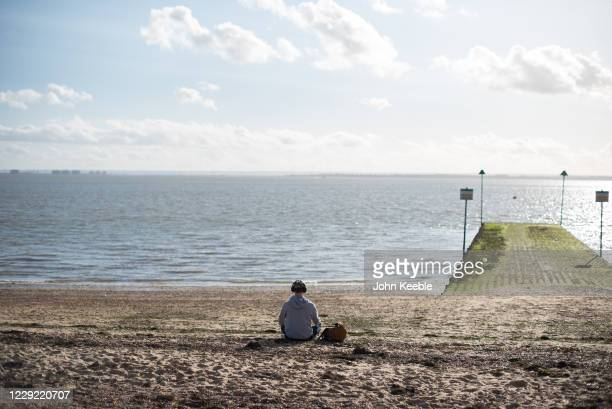 Young man listening to his earphones relaxes in the sunny weather on Chalkwell beach on October 22, 2020 in Chalkwell, Southend-on-Sea, England....