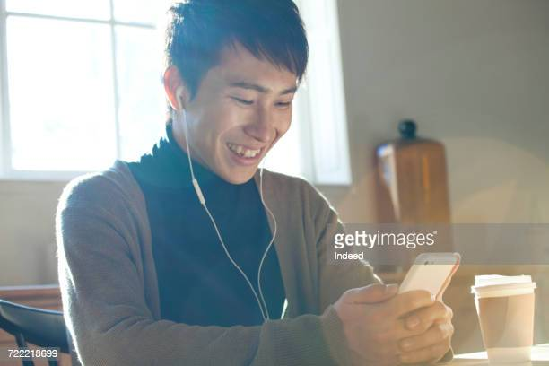 Young man listening to MP3 player at table