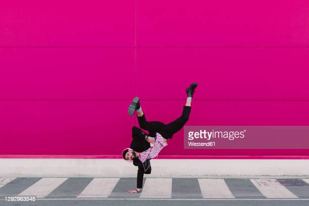 young man listening to music and dancing breakdance - hip hop music stock pictures, royalty-free photos & images
