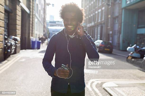 Young man listening to music from cell phone on urban street