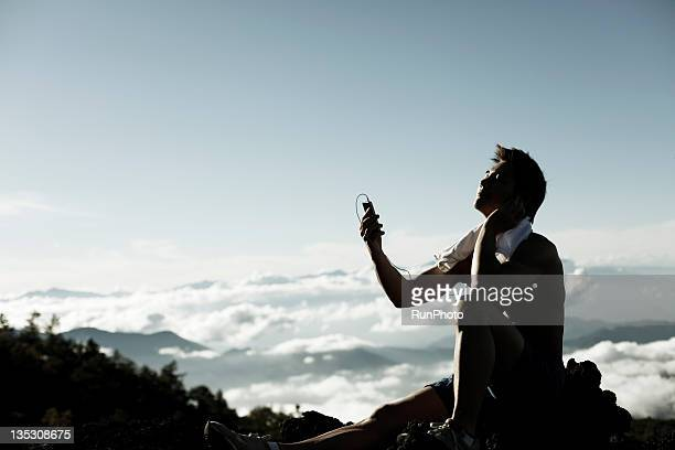 young man listening to music in the mountain