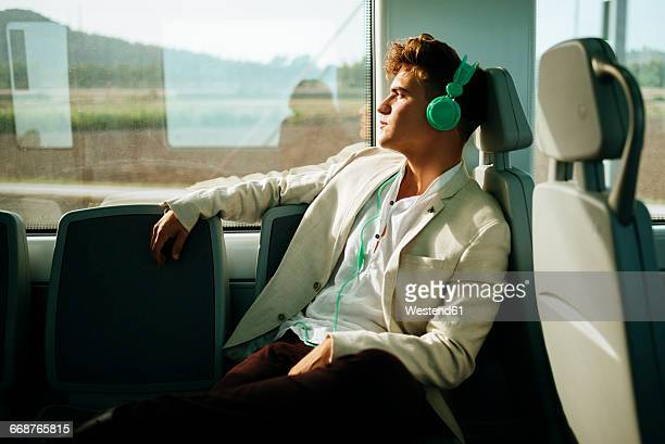 Young man listening to music on a train