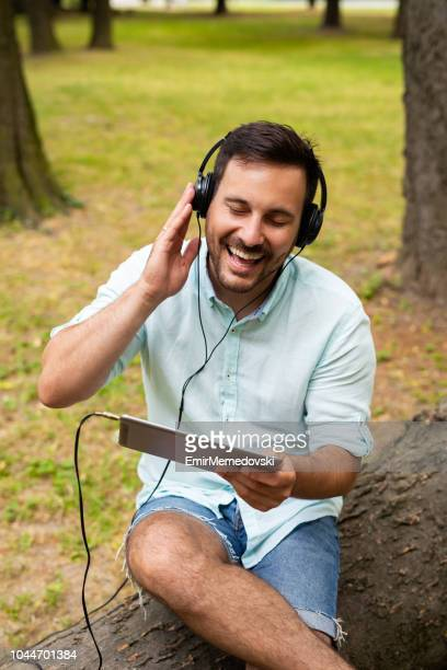 young man listening to music on digital tablet outdoors - emir memedovski stock pictures, royalty-free photos & images