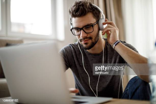 young man listening to music on laptop at home - webinar stock photos and pictures
