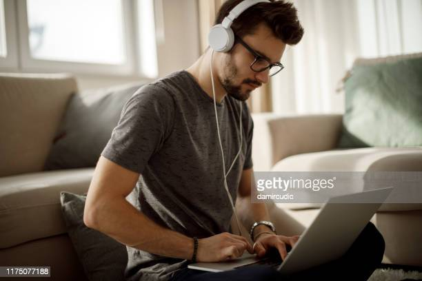 young man listening to music on laptop at home - damircudic stock photos and pictures
