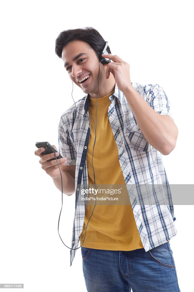 Young man listening to music on mobile phone : Stock Photo