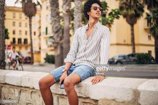 jeune homme écoutant la musique - short photos et images de collection