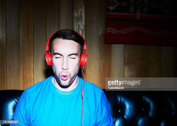young man listening to music wearing headphones