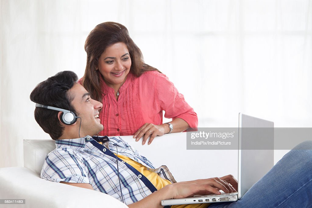 Young man listening to music while mother looks at laptop : Stock Photo