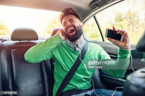 jeune homme écoutant la musique tout en voyageant - chanter photos et images de collection
