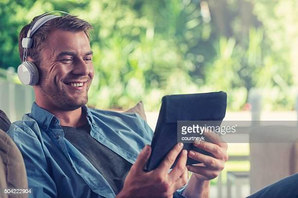 Jovem Ouvindo música com um tablet digital