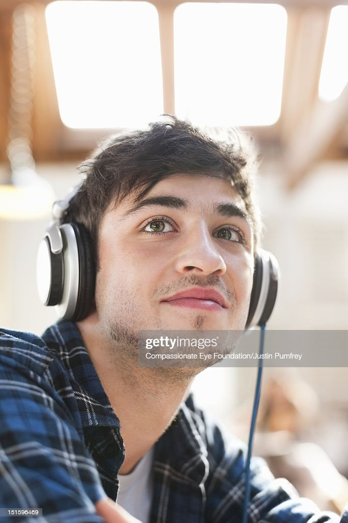 Young man listening to music with headphones : Stock Photo