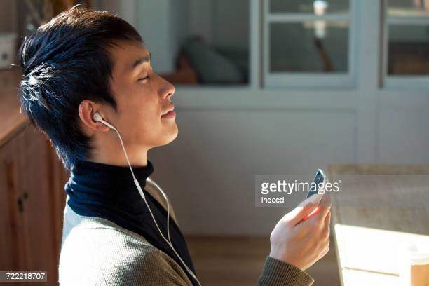 Young man listening to music with MP3 player in room
