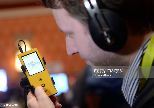 A young man listens to music using the music player 'Pono player 2' by manufacturer Pono Music founded by musician Neil Young during the...