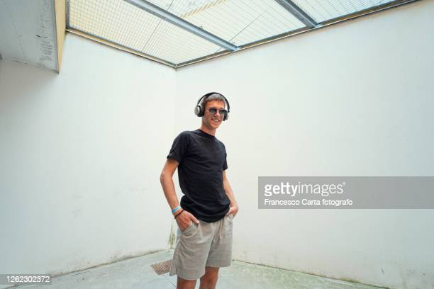 young man listens to music with headphones - tempio pausania stock pictures, royalty-free photos & images