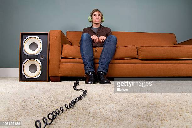 Young Man Listing to Headphones and Sitting on Couch