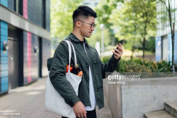 young man living a sustainable lifestyle - holding stock pictures, royalty-free photos & images