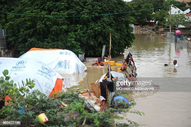 A young man living at a camp for the internally displaced wades in a chestdeep flooded street on May 20 2018 in Mogadishu after temporary shelters...