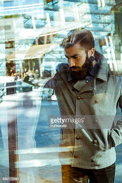 Young man (Hipster style) looking a window's shop