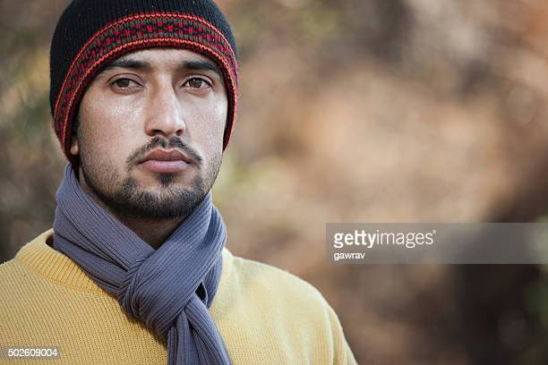 Young man looking at camera in winter outdoor scene.