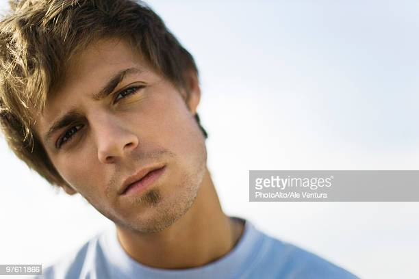 young man looking at camera with head tilted and brow furrowed - curiosity stock pictures, royalty-free photos & images