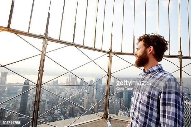 Young man looking at cityscape view, Empire State Building, New York City, USA
