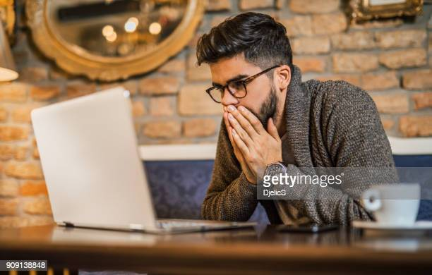 young man looking at computer. - news event stock pictures, royalty-free photos & images