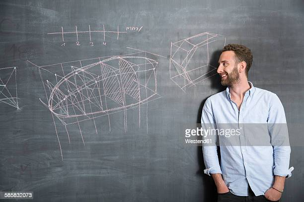 Young man looking at drawing at blackboard