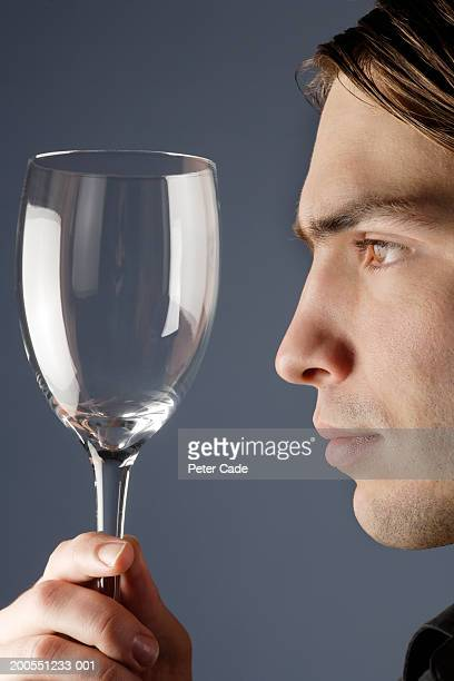 Young man looking at empty glass, close-up