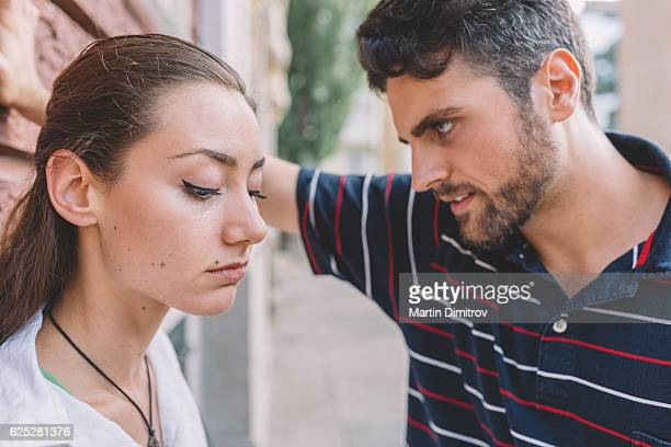 young man looking at his crying girlfriend - boyfriend stock pictures, royalty-free photos & images