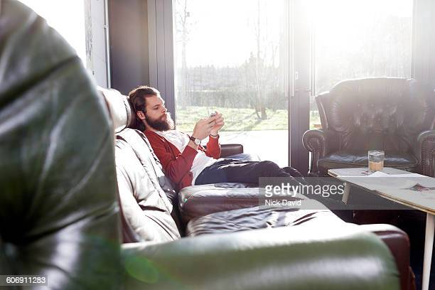 young man looking at his mobile phone - leather stock pictures, royalty-free photos & images