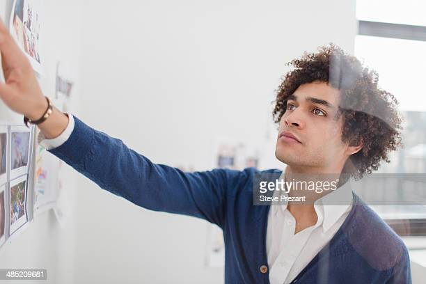 Young man looking at images on wall