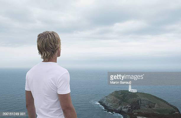 Young man looking at lighthouse on rock, rear view (Digital Composite)