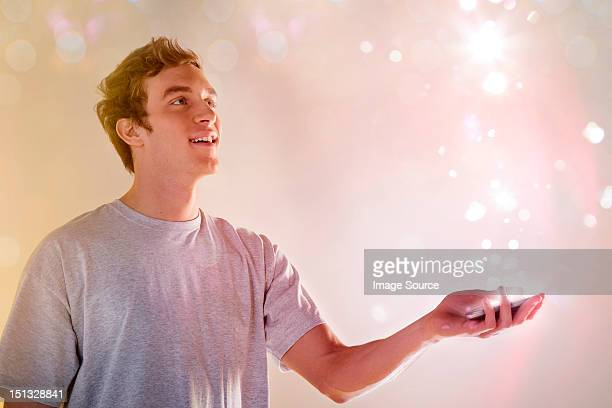 Young man looking at lights coming from cellphone