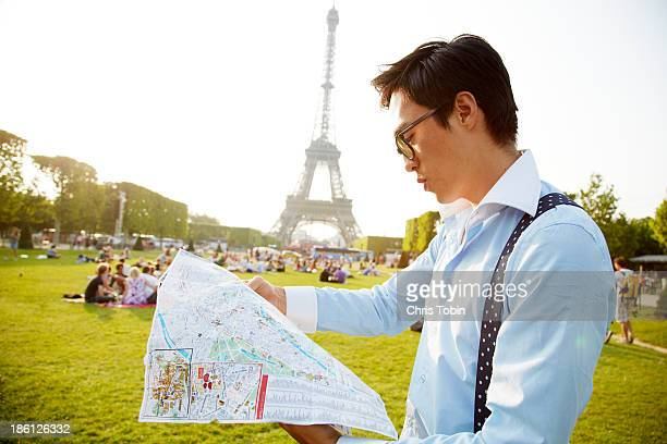 Young man looking at map near Eiffel Tower
